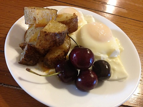 Poached eggs with roasted potatoes and cherries on the side