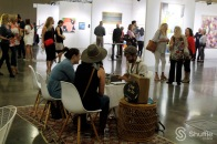 Ryan Ashley Knowles of Untouched Poetry chats with fellow art lovers to produce a poem for them at the Art City Fair reception on Friday April 29. / Photo by Ray Gilford